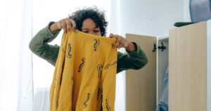 A girl holding up a yellow shirt with question marks on it