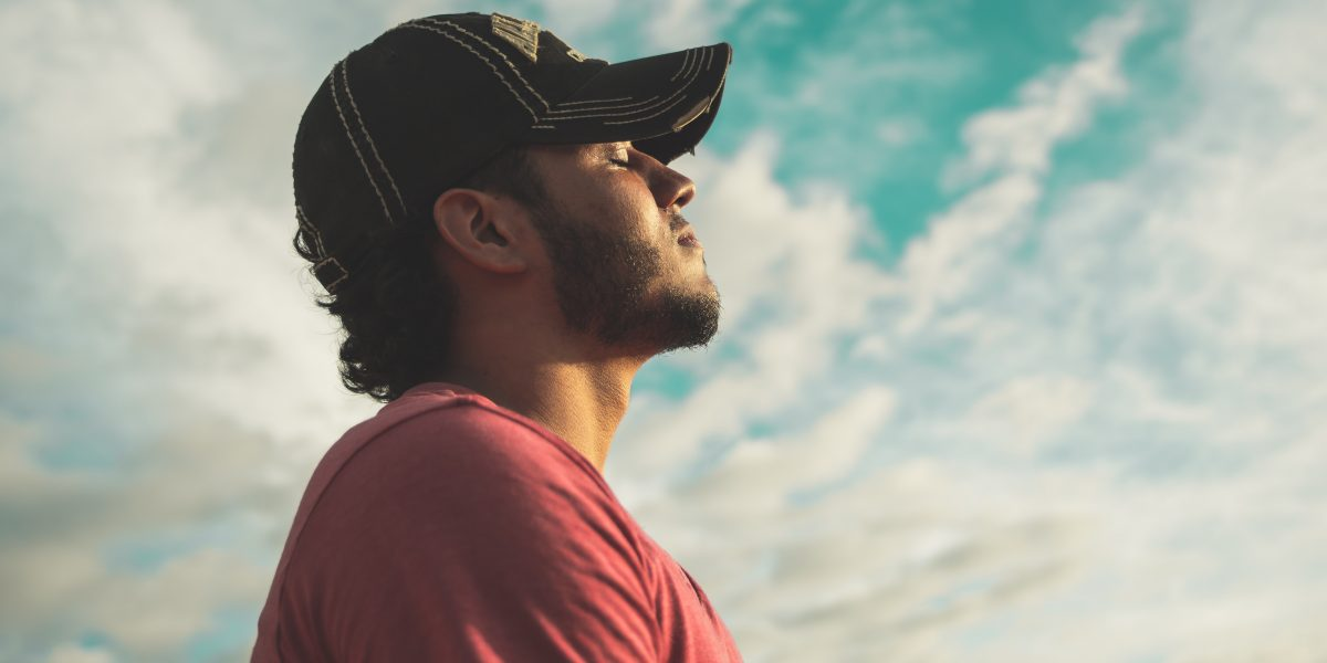 man-breathing-deeply-with-eyes-closed-under-cloudy-sky